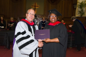 Chairman of the ABSW Board of Trustees Rev. Dr. Jim Hopkins presents M.Div. graduate Loretta Dickerson-Smith with her diploma.