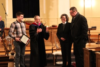 Rev. Abell is presented with her certificate. Pictured here, left to right: Some Guy, Church Moderator; Dr. Brian Henderson, Pastor; Rev. Jessica Abell; Thomas Giles, Jessica's husband