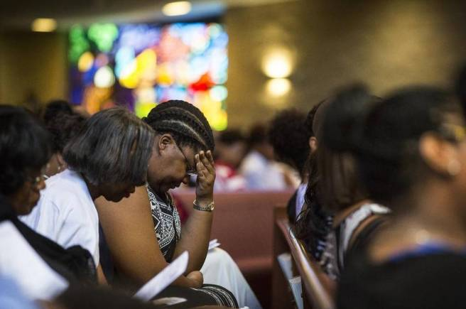Members of Friendship Missionary Baptist Church engage in a moment of silent prayer Sunday for Charleston